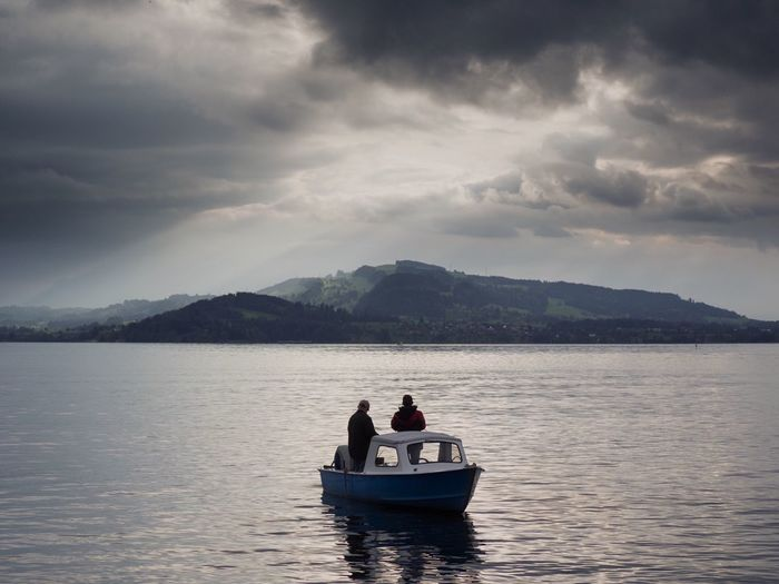 Dramatic Sky Storm Cloud Stormy Weather Dramatic Sky Nautical Vessel Water Sky Transportation Cloud - Sky Mode Of Transportation Two People Beauty In Nature Lake Nature Adult Scenics - Nature Mountain Real People Leisure Activity Waterfront Outdoors 2018 In One Photograph