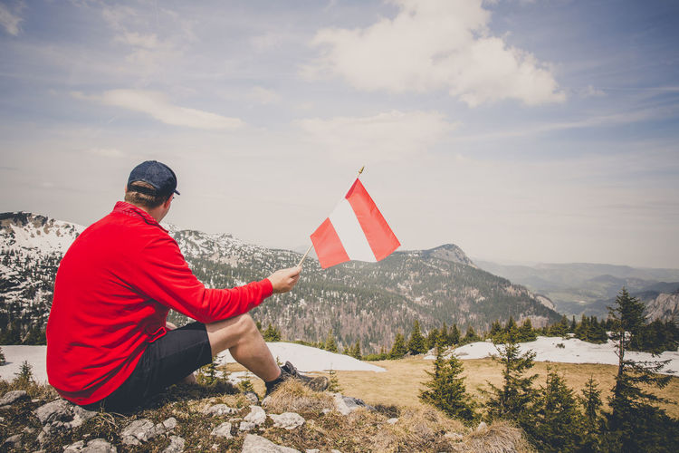 hiker with red sweater is holding an austria flag in the mountains Beauty In Nature Cloud - Sky Day Flag Freedom Full Length Leisure Activity Lifestyles Looking At View Men Mountain Mountain Range Nature One Person Outdoors Patriotism Real People Red Scenics - Nature Sitting Sky Tranquility