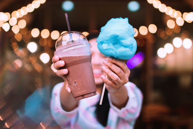 Close-up of woman holding cold coffee and cotton candy outdoors at night