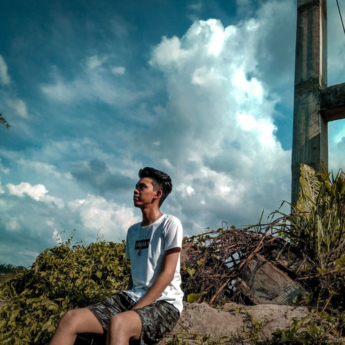 Young man sitting on land against sky
