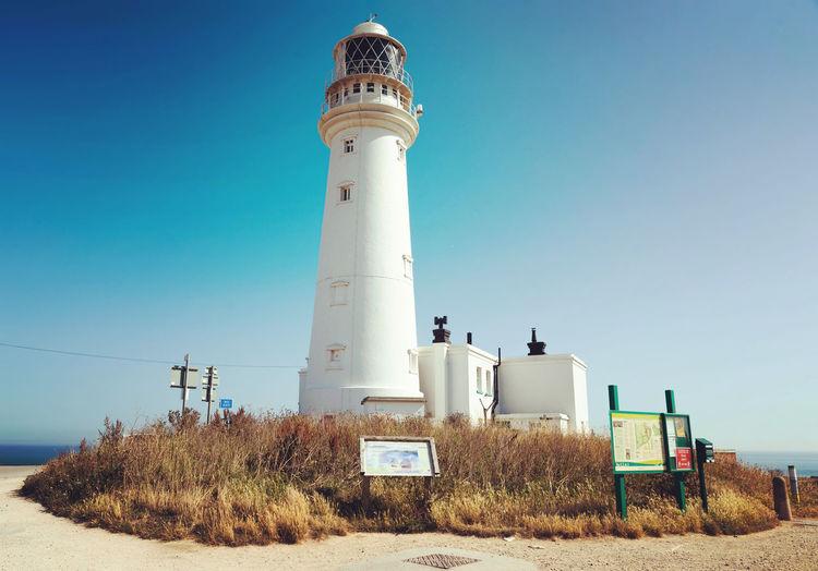 Lighthouse on field against clear blue sky