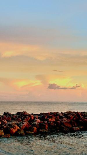 Sunset Sea Sky Beach Cloud - Sky Tranquil Scene Landscape Horizon Over Water Outdoors Sun Beauty In Nature No People Travel Destinations Water Nature Sunlight Seascape Orange Color Dramatic Sky Beauty In Nature Relaxation Rock - Object Waterfront