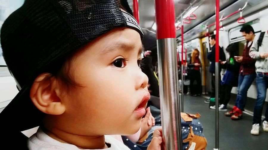 Close-up of innocent boy looking away while traveling in metro train