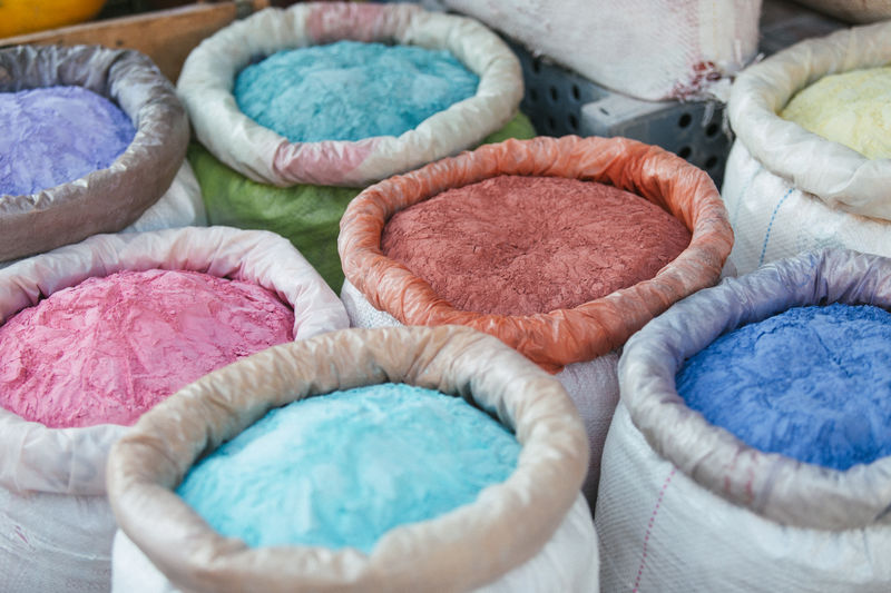 High angle view of multi colored powder paint in sacks
