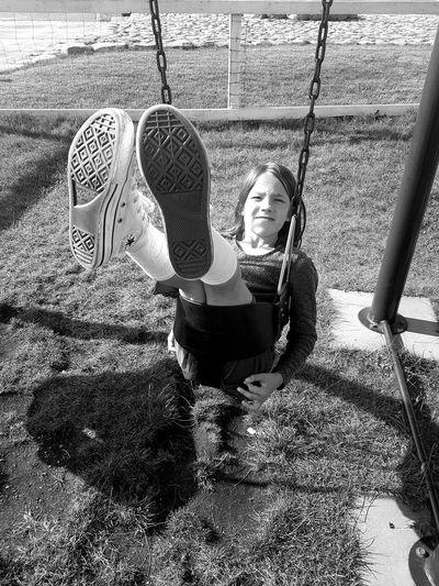Full length portrait of girl on swing in playground
