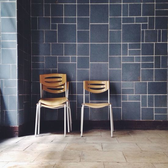 Empty chairs against tiled wall