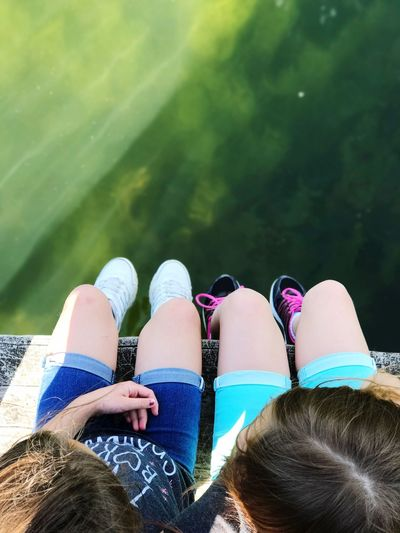 Low section of girls sitting over lake