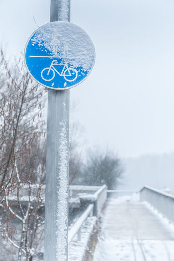 Bridge Bridge Railing Cold Temperature Day Frozen Nature No People Outdoors Pole Road Sign Sky Snow Snowbound Snowing Traffic Sign Tree Winter