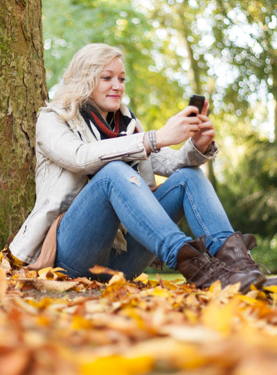 Attractive young woman using smart phone Autumnal Colours Autumnal Leaves Autumnal Mood Casual Clothing Caucasian Cell Phone  Communication Fall Colors Fall Season Mobile Phone Outside Person Smart Phone Smartphone Text Message Text Messaging Young Adult Young Woman Women Around The World