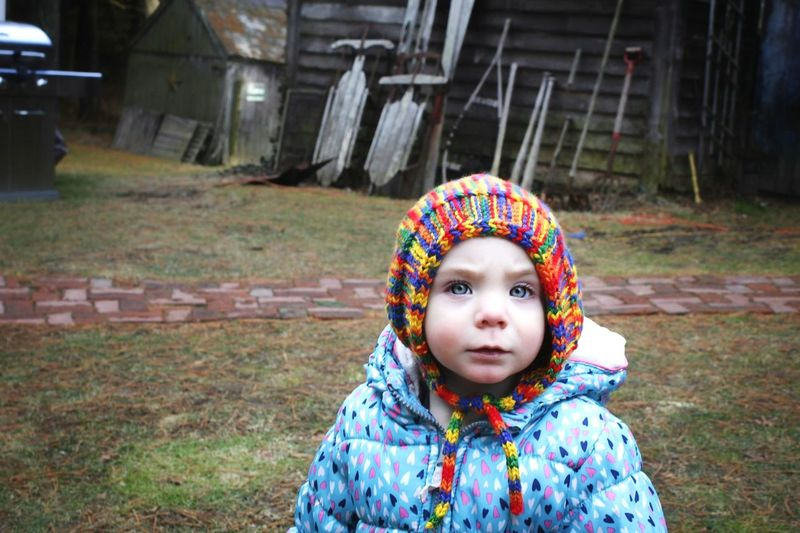 Portrait of baby girl in warm clothes standing outdoors