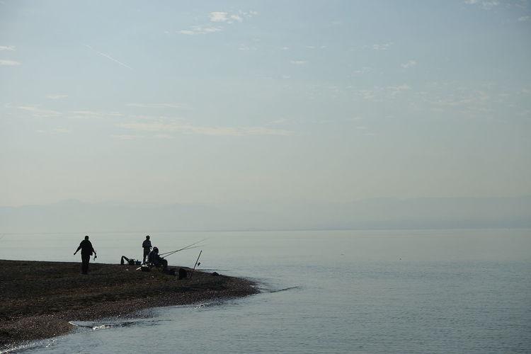 Silhouette men fishing by sea against sky