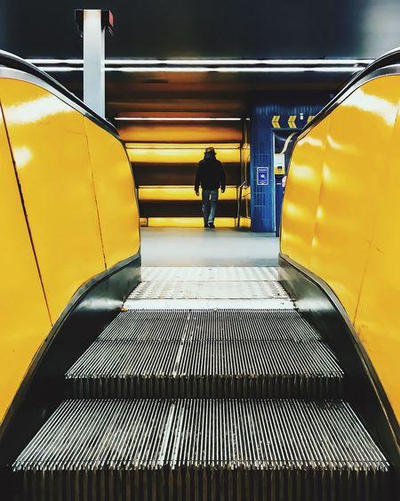 Rear view of man walking in building seen through escalator