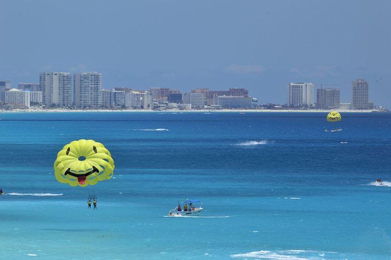 Smiley face parachutes over sea against clear sky