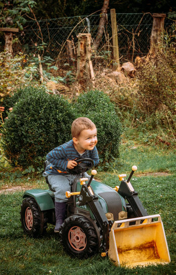 Full length of boy with tractor in park