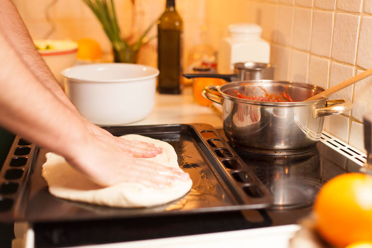 Cropped Hands Kneading Dough In Tray