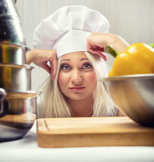 Portrait Of Young Woman With Head In Hands Standing In Kitchen