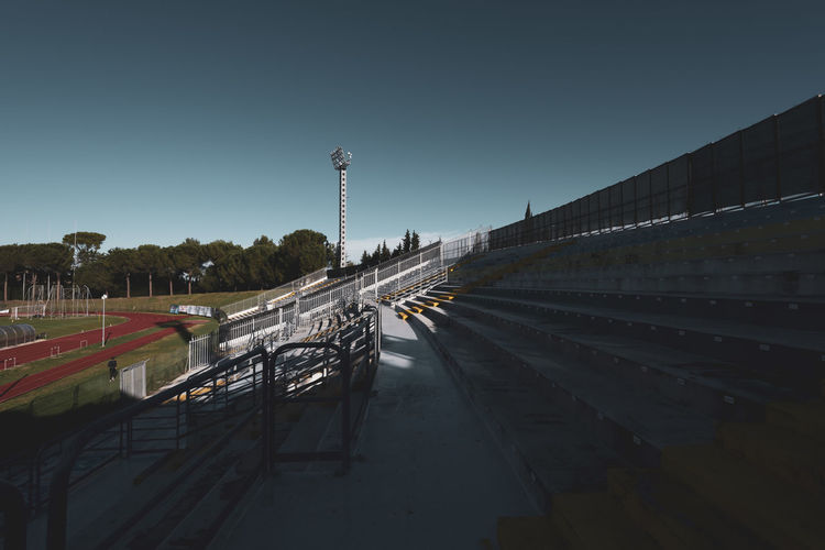 Sport Stadium Soccer Athletic Movement Nature Mountain Range Panorama Landscape View Steps Bleachers Light Pylons Architecture Cement Small Grass Track Implant Running Competition Football Play Seats Goal Field Dribbling Poles Match Contest Training Practice Built Structure Outdoors Barrier Building Exterior No People