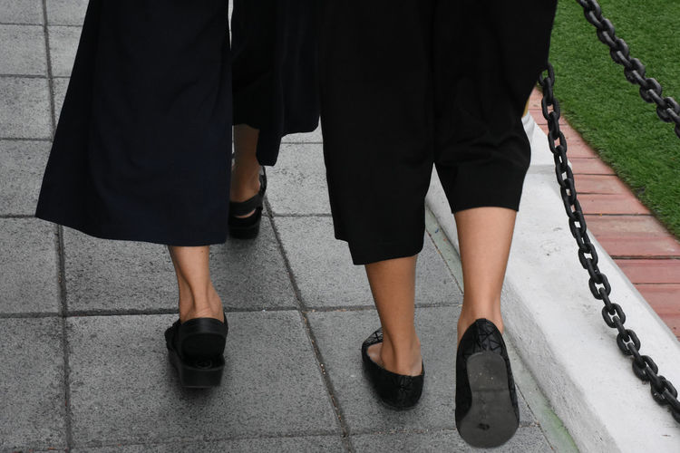 Low section of women walking on footpath