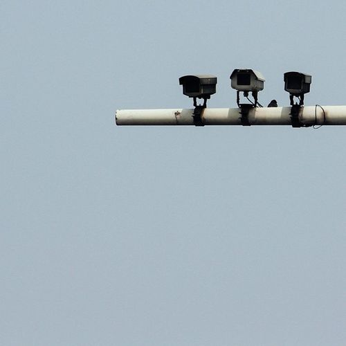 Three Surveillance Cameras Against Clear Sky