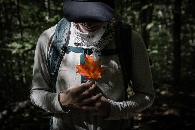 Midsection of man holding orange leaf in forest