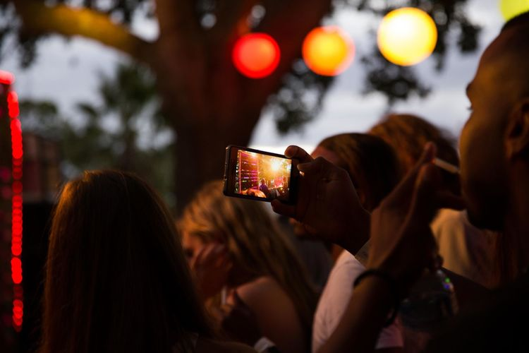 Portrait of woman photographing illuminated smart phone