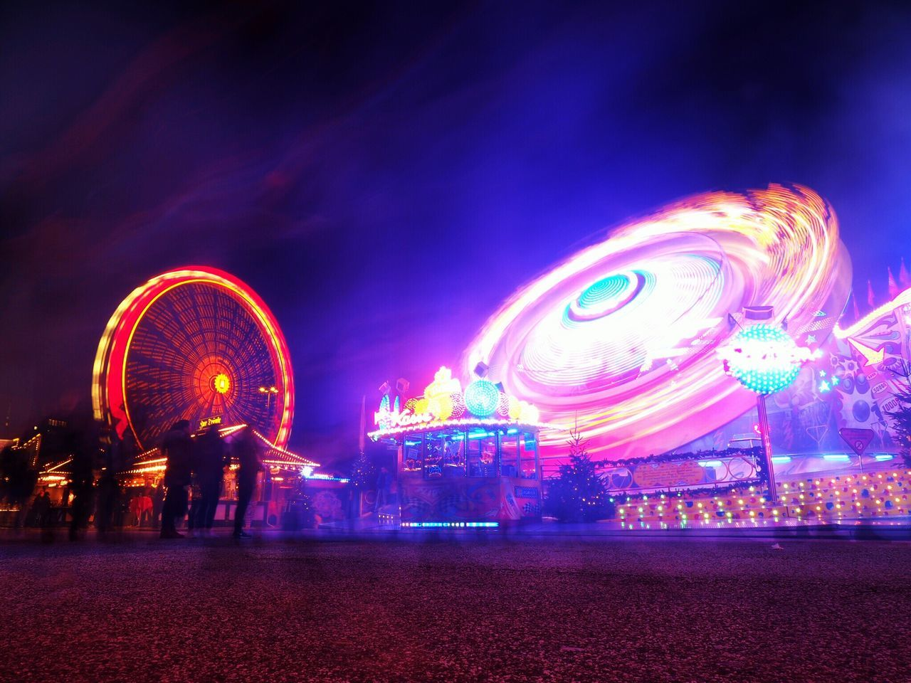 amusement park, amusement park ride, arts culture and entertainment, illuminated, night, motion, sky, long exposure, ferris wheel, architecture, spinning, multi colored, blurred motion, nature, leisure activity, enjoyment, built structure, outdoors, group of people, cloud - sky, nightlife
