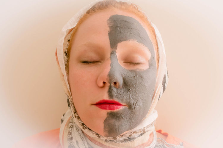 Close-Up Of Young Woman With Mud Facial Mask Against White Background