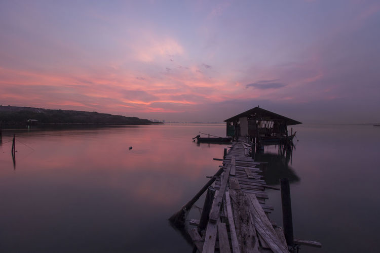 Water Sky Sunset Cloud - Sky Beauty In Nature Scenics - Nature Tranquil Scene Tranquility Architecture Built Structure Sea Nature Pier Orange Color No People Idyllic Reflection Jetty Outdoors moments of happiness Sunrise Rural Scene Island Vacations Nature Peace Reflection Wood - Material Old Penang