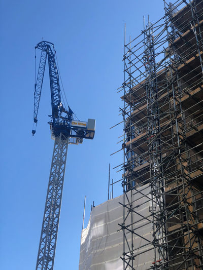 Low angle view of cranes at construction site