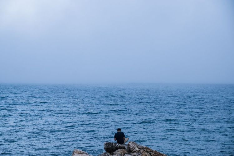 Rear view of man sitting on rock by sea against clear sky