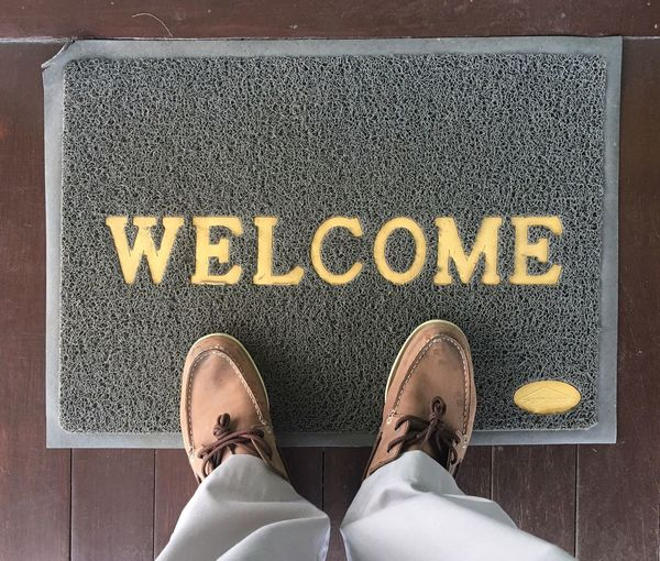 Shoe Low Section Text Human Leg Western Script Standing One Person Communication Personal Perspective Welcome Sign Human Foot Human Body Part High Angle View Black Color Real People Lifestyles One Man Only Men Day Indoors  Top View Door Carpet Doormat