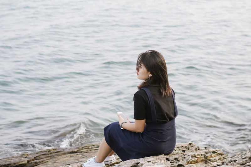 Young woman sitting on shore against sea