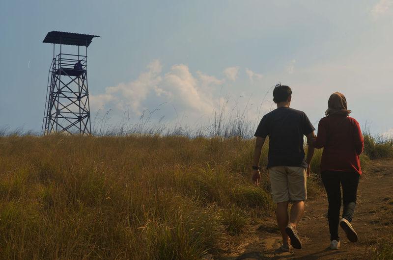 Rear View Of Couple Walking On Field Against Sky