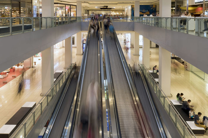 Escalators inside a shopping center, blurred motion Architecture Blurred Shops Unrecognizable People Brands  Columns Commerce Escalator Illuminated Interior Leisure Time Plans Purchases Shop Windows Shopping Mall Structure
