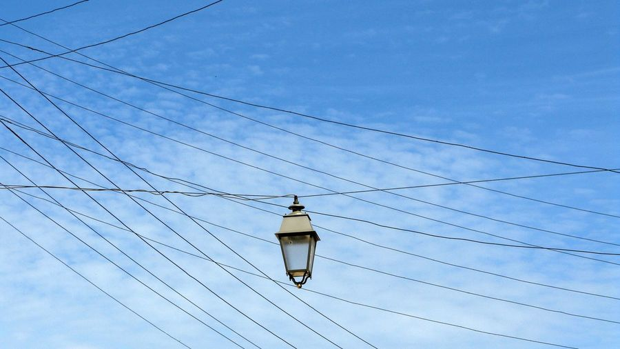 Low angle view of lighting equipment hanging from cable against blue sky