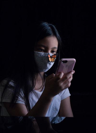 Girl using smart phone against black background