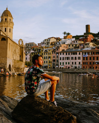 Woman sitting by canal against buildings in city