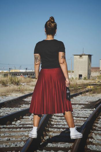 Rear view of woman on railroad tracks against clear sky