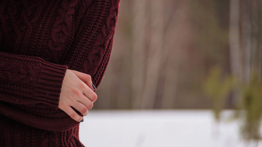 Midsection of woman wearing sweater while standing at park during winter