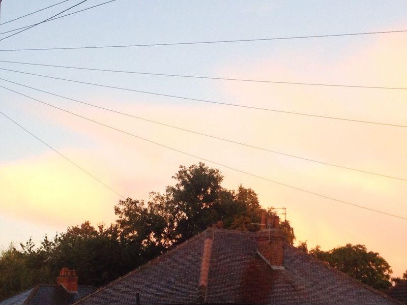 Wet Roof Phone Lines Orange Clouds Chimneys