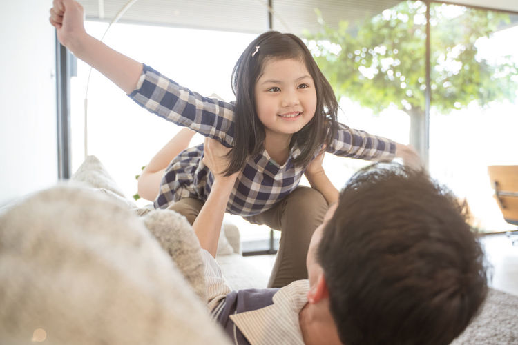 Happy little girl daughter playing with father while ride dad back and dad lying on the bed at home Asian  Family Happiness Happy Happy People Family Time Home House Daughter Parent Father Mother Dad Mom Love Lifestyles Living Room ASIA Japanese  Korean Thai Taiwan Smiling Smile Fun Portrait Girls Flying Fly Playing Play