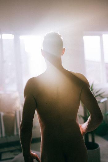 Rear view of shirtless man at home