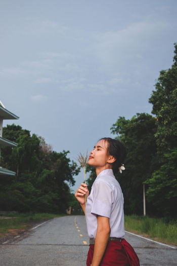 Side view of girl standing by tree against sky