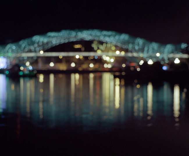 Defocused image of illuminated lights on river at night
