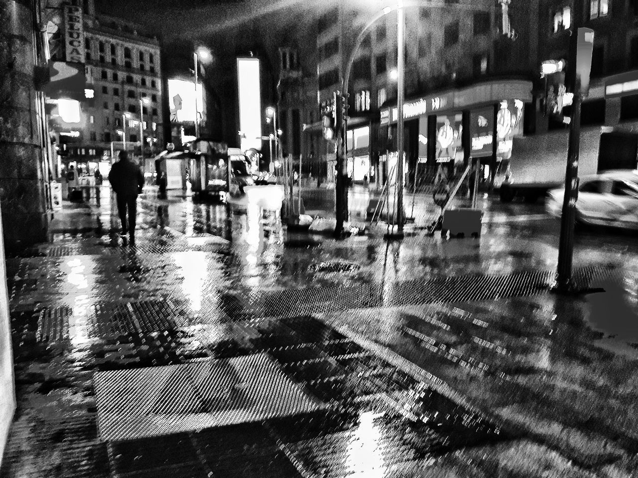 city, illuminated, architecture, street, night, wet, building exterior, transportation, city life, rain, group of people, built structure, motion, reflection, walking, incidental people, real people, mode of transportation, land vehicle, rainy season, city street, outdoors