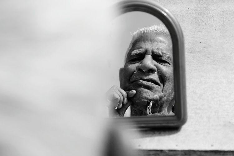 Senior man shaving reflecting on mirror