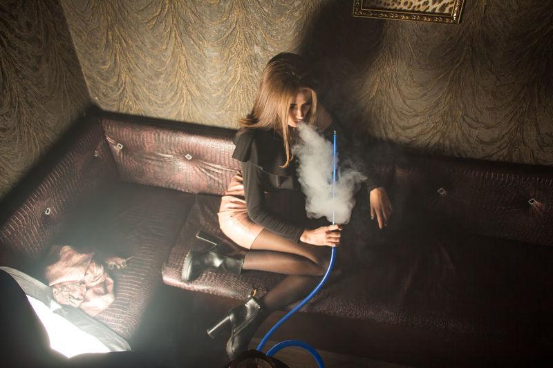 High angle view of woman smoking hookah while sitting on sofa