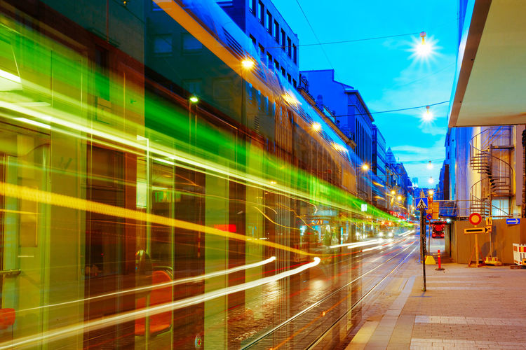 Blurred Motion Of Cable Car By Buildings In Illuminated City During Sunset
