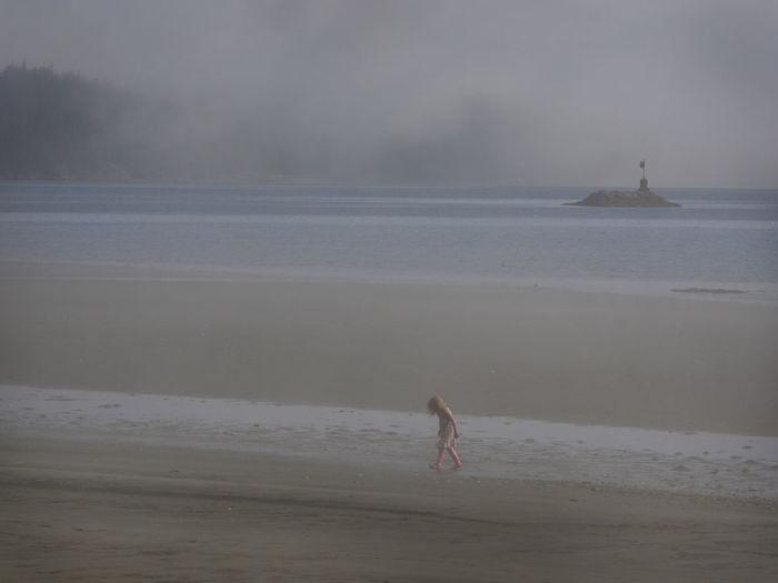 Girl Walking At Beach Against Cloudy Sky