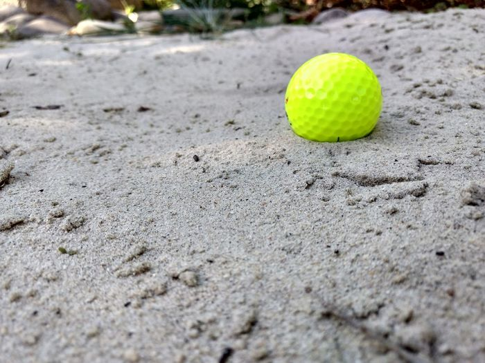 Close-up of yellow ball on sand